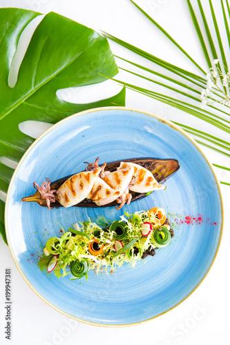 egzotyczne-danie-na-niebieskim-talerzu-oraz-zielone-liscie-na-bialym-tle