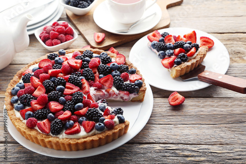 Tela Sweet tart with berries on grey wooden table