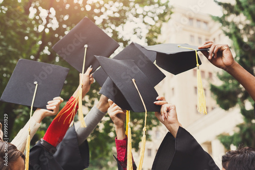 A group of graduates throwing graduation caps in the air Fototapet