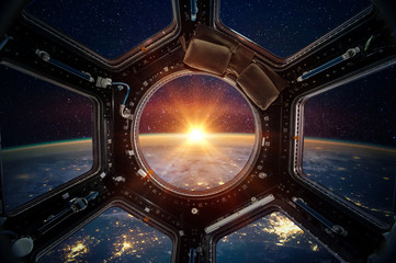 Earth and galaxy in spaceship international space station window porthole. Elements of this image furnished by NASA