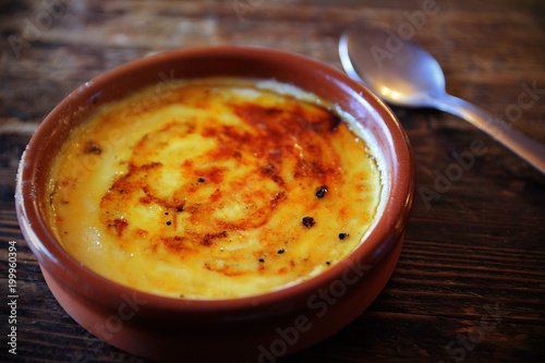 Fotografie, Obraz  Typical crema catalana served on a clay plate on a rustic wooden table with a spoon