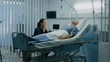 In the Hospital Ward Recovering Father is Visited by Daughter. Senior Sick Man Sleeping in Bed Daughter Sits Beside, Worrying. Shot on RED EPIC-W 8K Helium Cinema Camera.