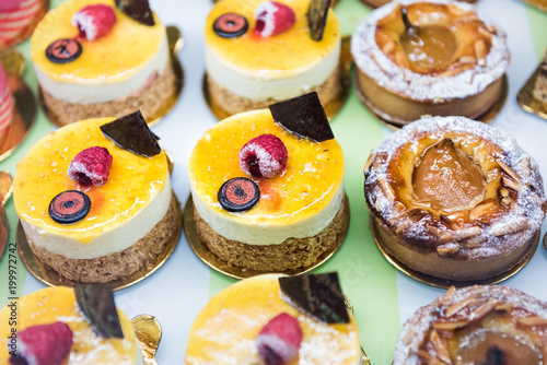 Foto op Aluminium Vruchten Many different selection variety of mini small cakes, pastries on display in bakery shop store with halloween cream decorations, raspberry tart