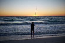 Silhouette Of Man Fishing In Sea