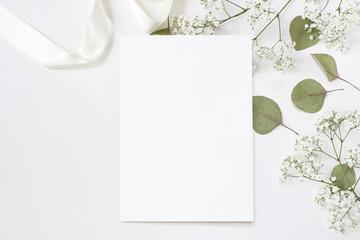 Styled stock photo. Feminine wedding desktop stationery mockup with blank greeting card, baby's breath Gypsophila flowers, dry green eucalyptus leaves, satin ribbon and white background. Empty space