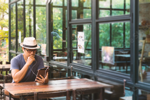 Asian men using a tablet in coffee shop. Poster