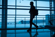 Silhouette of girl walking on airport terminal