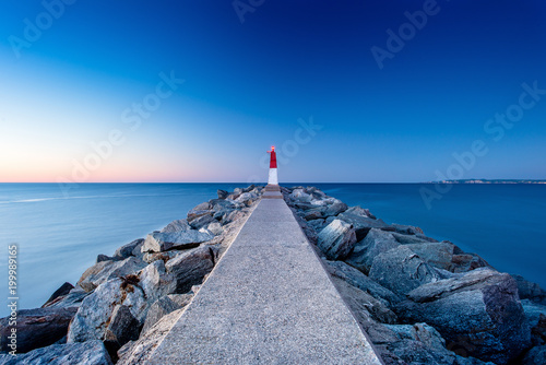 Fotobehang Natuur Park Evening landscape with a pier and a lighthouse in Empuriabrava, Spain
