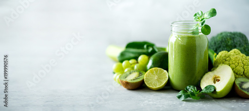 Glass jar mugs with green health smoothie, kale leaves, lime, apple, kiwi, grapes, banana, avocado, lettuce. Copy space. Raw, vegan, vegetarian, alkaline food concept. Banner