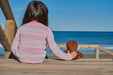 Lovely Close-up Of Little Girl Accompanied By Her Friend Toy Brown Monkey Sitting On A Wooden Stairs Accessing The Beach Looking At The Sea