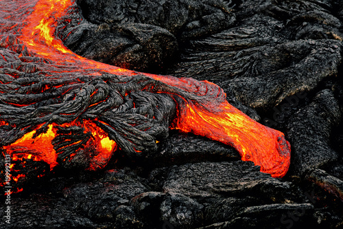 Hot magma escapes from an earth column as part of an active lava flow, the glowi Fotobehang