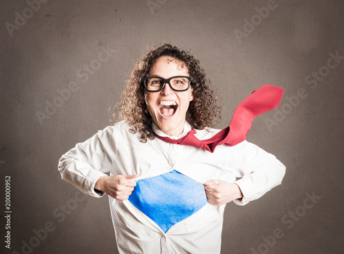 Photographie  woman opening her shirt like a superhero on a gray background
