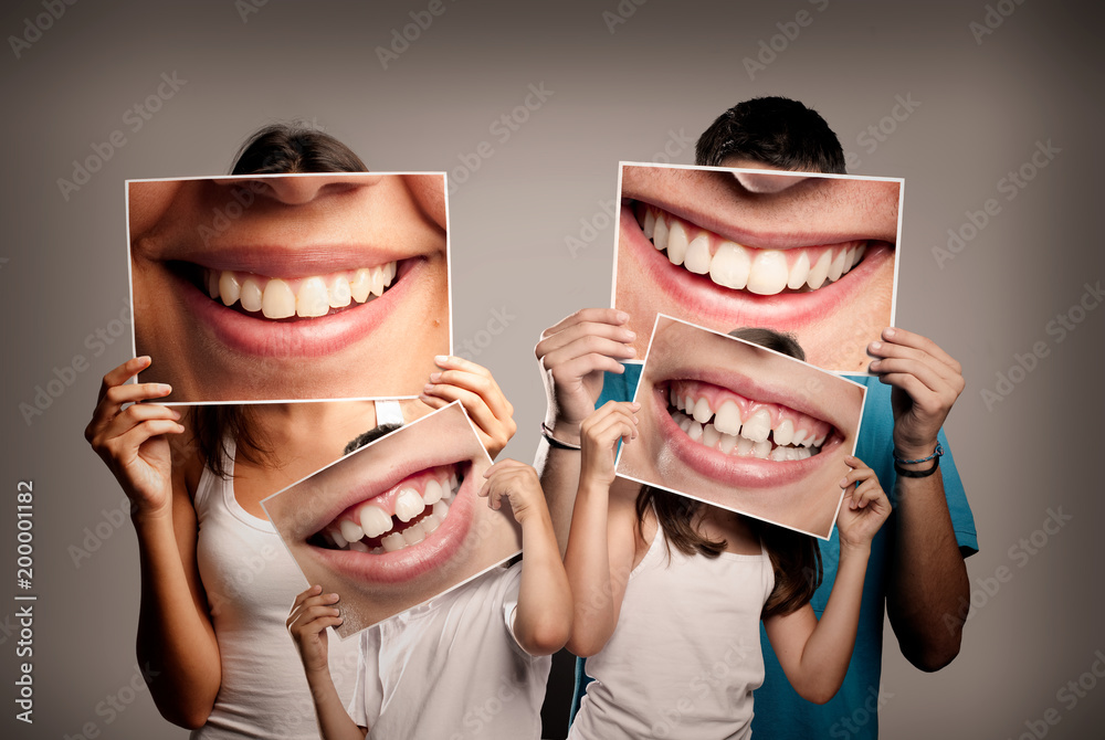 Fototapeta young family with children holding a picture of a mouth smiling on a gray background