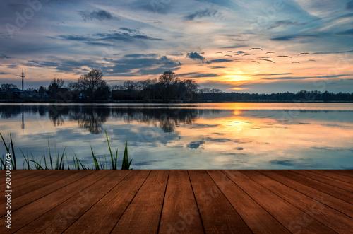Cisza na jeziorze - drewniane molo o zachodzie słońca
