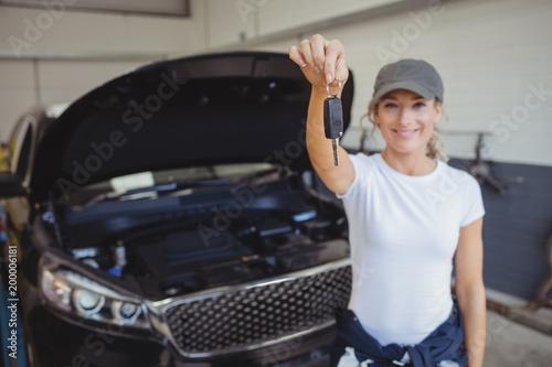Female mechanic in garage holding car key