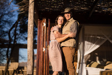 Couple Embracing Each Other In Cottage During Safari Vacation