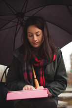 Woman Using Digital Tablet While Holding Umbrella