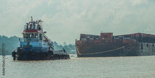 Carta da parati Tugboat pulling heavy loaded barge of black coal in the Mahakam river, Indonesia
