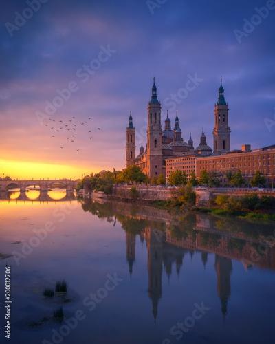 Basilica del Pilar and Puente de Piedra reflected in the Ebro river during a beautiful sunrise, Zaragoza