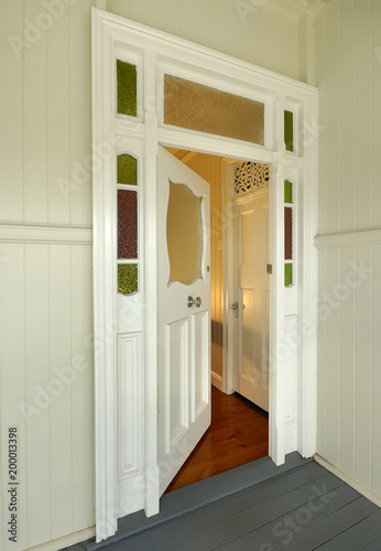Photo Door to old colonial style wooden home, slightly open with warm interior light in Queensland Australia