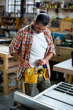Carpenter Removing Spirit Level From Tool Belt