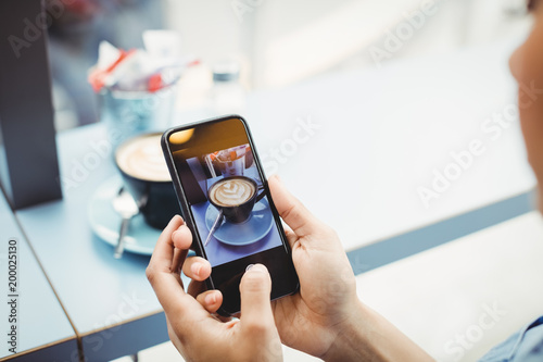 Woman holding mobile phone with photograph of coffee