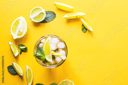 Ice tea with ice, lemon and mint on a combined colored yellow background. Summer cold drink cocktail. Top view, flat lay