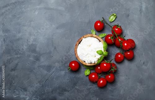 Plakat Miękki ricotta ser w drewnianej misce z zielonym basilem i czereśniowymi pomidorami, szarość kamienny tło, odgórny widok