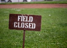 """""""Field Closed"""" Sign Blocking Access To A Field In A Park"""