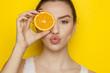 Leinwandbild Motiv Young woman posing with slice of orange on her face on yellow background