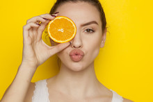 Young Woman Posing With Slice Of Orange On Her Face On Yellow Background