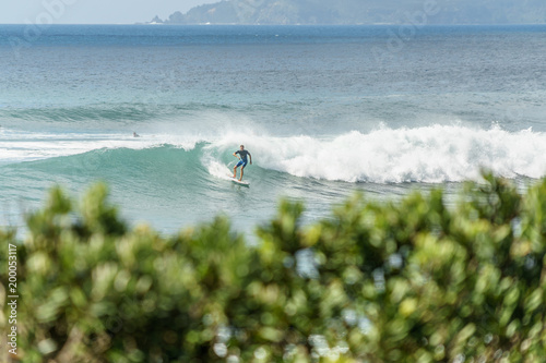 man riding on waves with surfboard on cloudy day, Leigh beach, New Zealand Wallpaper Mural