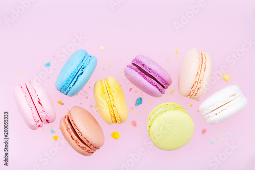 Fototapeta Flying colorful macaron or macaroon on pink pastel background.
