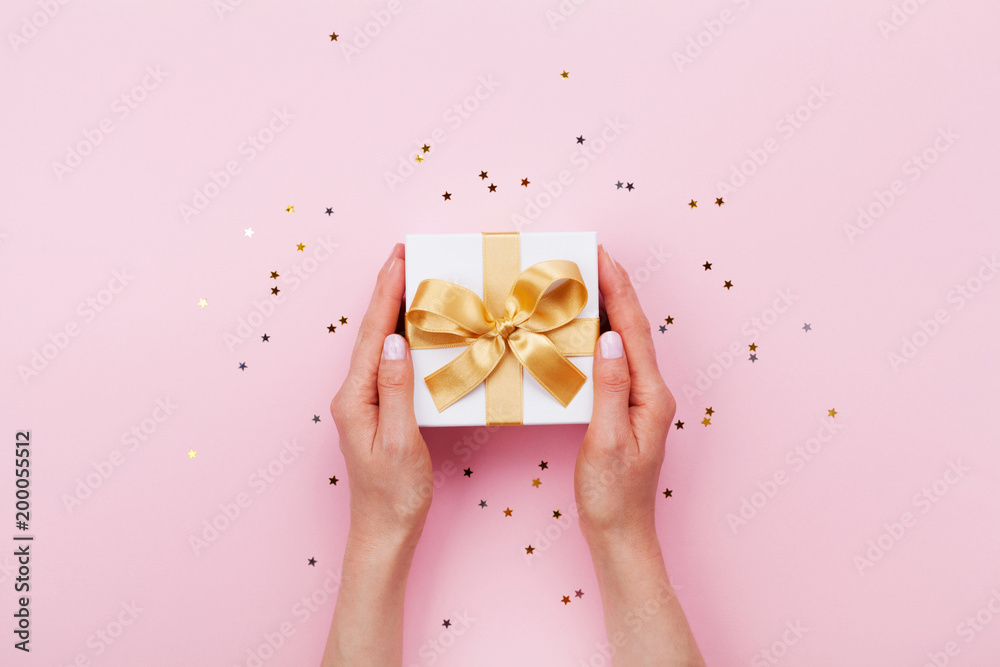 Fototapeta Womans hands holding gift or present box decorated confetti on pink pastel table top view. Flat lay composition for birthday or wedding.
