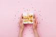 canvas print picture - Womans hands holding gift or present box decorated confetti on pink pastel table top view. Flat lay composition for birthday or wedding.