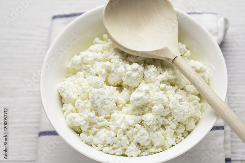Staande foto Zuivelproducten cup with cottage cheese, wooden spoon on white towel close-up.