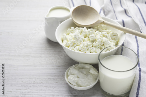 Foto auf Leinwand Milchprodukt dairy products, cottage cheese, milk in a glass, yogurt, sour cream in a white dish on a white background.