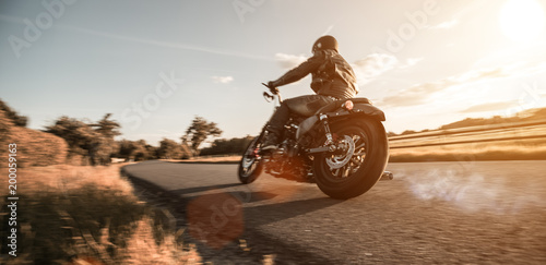 Fotobehang Fiets Man riding sportster motorcycle during sunset.