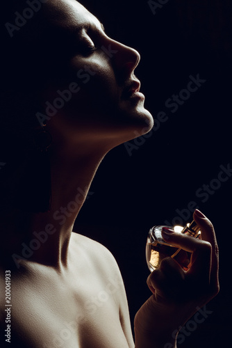 Fototapeta silhouette of sensual girl spraying perfume on neck, isolated on black obraz
