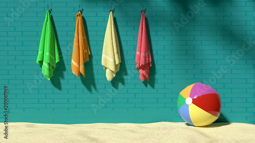 Photo Four colorful fluffy towels hanging on the turquoise brick-like wall with a beac