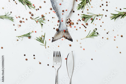 Fotografía Raw fish with cutlery and rosemary with pepper isolated on white