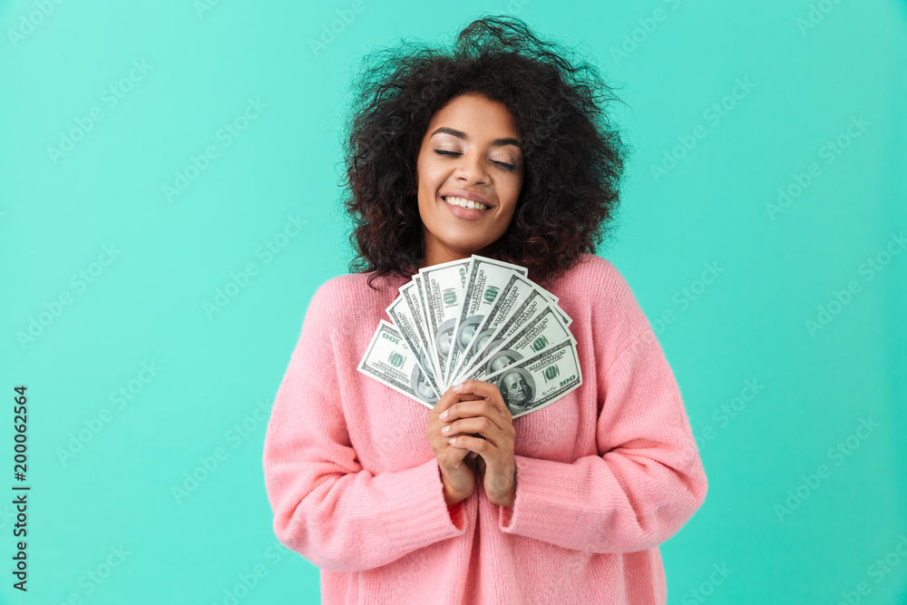 Fototapety, obrazy: Portrait of excited woman 20s with afro hairstyle pointing finger on fan of money dollar bills, isolated over blue background