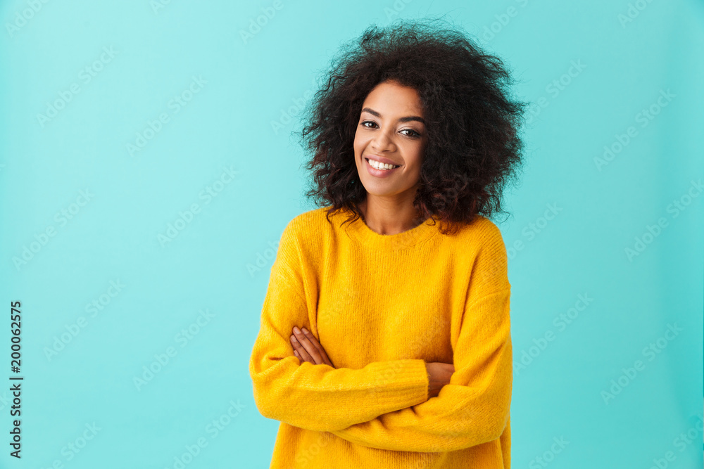 Fototapety, obrazy: Happy brunette woman in yellow shirt looking on camera with perfect smile standing with arms crossed, isolated over blue background