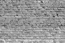 Brick Wall. The Bricks Cracked. Masonry Is Uneven. Wall Is Covered Or Stained With Cement Mortar. Laying With Alternation. Many Layers. There Are Broken Bricks. Background, Backdrop Or Wallpaper.
