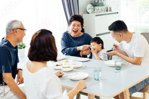Fotografia  Happy Asian extended family having dinner at home full of laughter and happiness