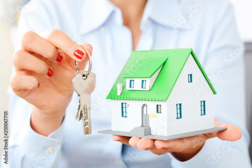 Zdjęcie XXL Bizneswomanu mienia miniatury dom i klucz, nieruchomości transakci pojęcie