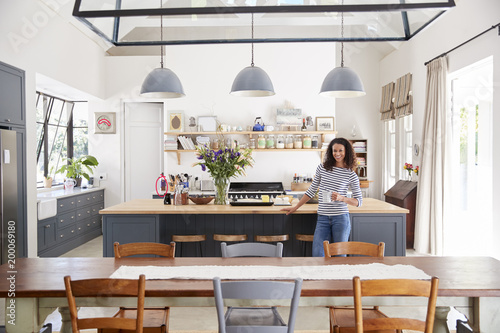 Fotografía  Mixed race woman in open plan kitchen looking to camera