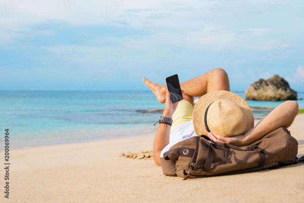 Fototapety, obrazy: Guy with smartphone lying on the beach