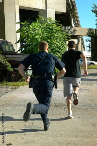 Fotografía  Policeman chasing after suspect man
