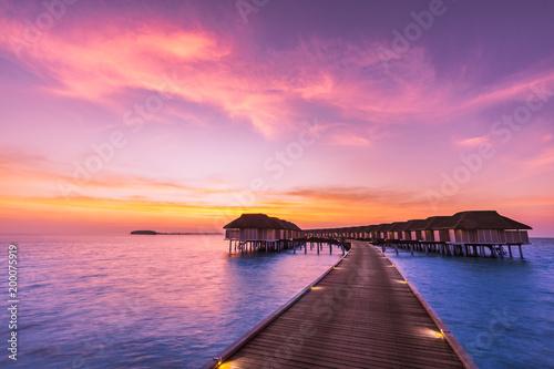 Sunset on Maldives island, luxury water villas resort and wooden